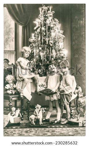 happy kids with christmas tree, gifts and vintage toys. antique sepia picture with original film grain - stock photo