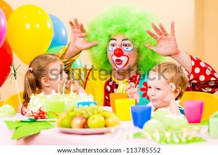 happy kids with clown on birthday party - stock photo