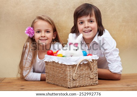 Happy kids with easter bunny and colorful eggs in a basket- shallow depth of field - stock photo