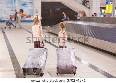 Happy kids with luggage inside airport going on vacations trip  - stock photo