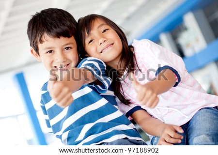 Happy kids with thumbs up and smiling - stock photo