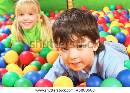 Happy lad looking at camera with smile on background of cute girl - stock photo