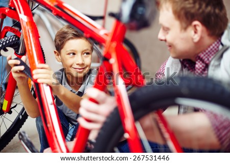 Happy lad looking at his father while helping him in garage - stock photo