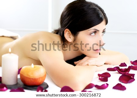 Happy lady in spa with candle and roses