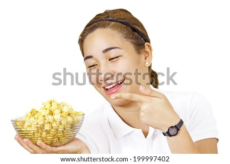 Happy lady pointing to a bowl of popcorn. - stock photo