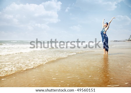 Happy lady standing in the water with hands up. Summer beach in Goa, India. Horizontal photo with vibrant colors - stock photo