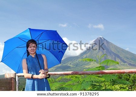 Happy lady tourist with a beautiful volcano at the background. - stock photo