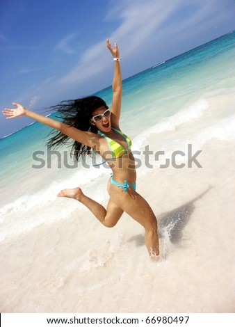 Happy latin young woman runing on the beach. - stock photo