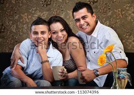 Happy Latino family of three embracing on a sofa - stock photo