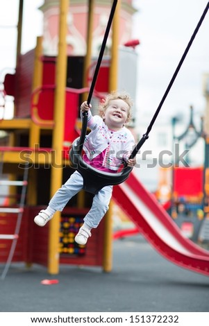 Happy laughing baby girl in a swing on a playground - stock photo