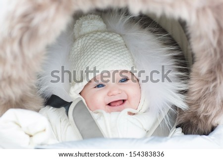 Happy laughing baby girl in a warm stroller wearing a winter jacket and a hat on a walk in a park - stock photo
