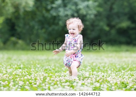 Happy laughing baby girl running in a clover field - stock photo
