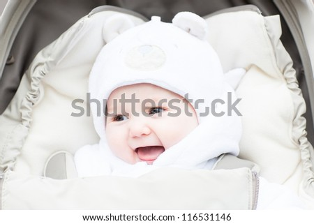 Happy laughing baby in a warm hat sitting in a stroller on a winter day - stock photo