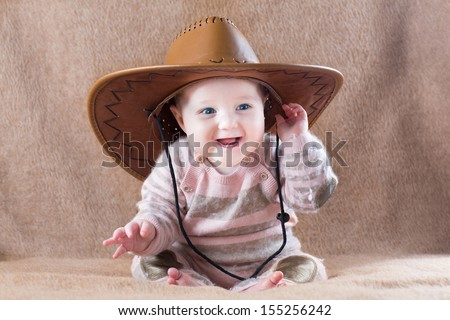 Happy laughing baby wearing a cow girl outfit with a big hat - stock photo