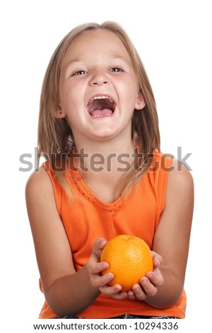 Happy laughing child holding a orange