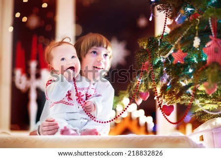 Happy laughing children playing under a beautiful Christmas tree - stock photo