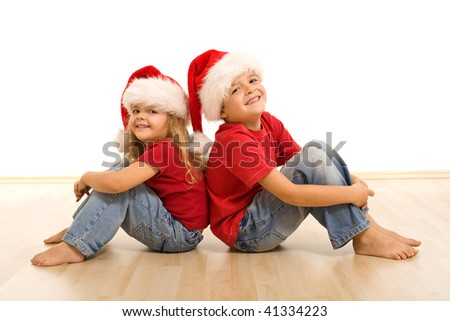 Happy laughing christmas kids sitting on the floor - isolated - stock photo