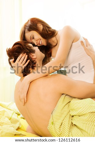 Happy laughing couple of young attractive adults in the bed - stock photo