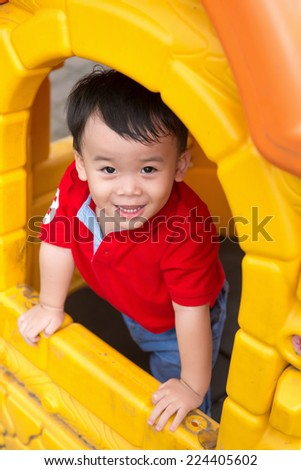 Happy laughing cute little three years old asian child boy or kid playing in a yellow house on a playground. Healthy lifestyles concept. Happiness without limit, happy asian child outdoor, face focus. - stock photo