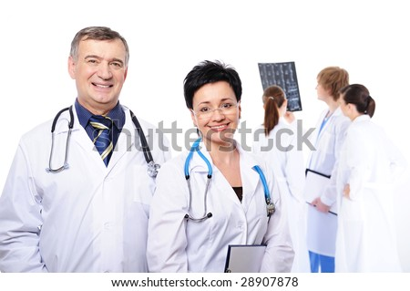 happy laughing doctors at foreground and three doctors studying X-ray