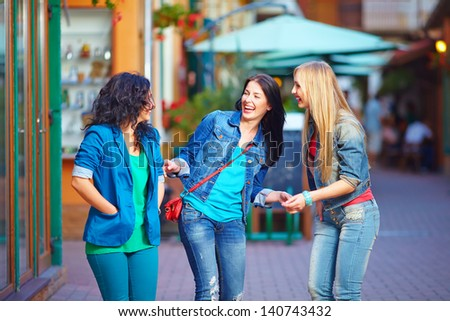 happy laughing friends on evening street - stock photo