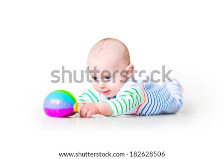 Happy laughing funny baby boy wearing a colorful shirt learning to crawl playing on his tummy, on white background - stock photo
