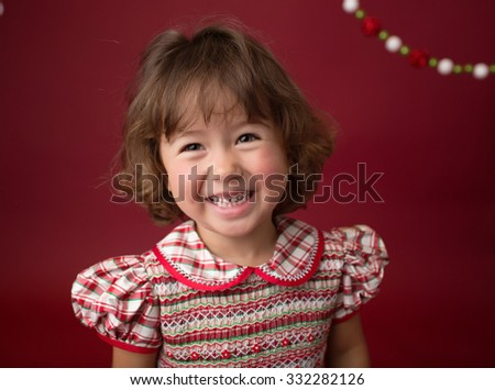 Happy, laughing girl, child in a Christmas dress, sitting on a sled with christmas trees and ornaments on red background. X-mas happiness concept. - stock photo