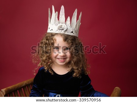 Happy, Laughing girl, Christmas or winter holiday themed setup on red background, princess in a crown - stock photo
