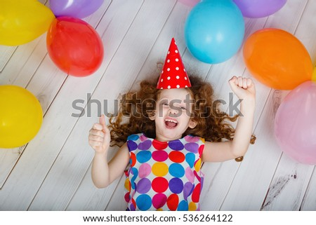Happy laughing girl showing thumbs up on birthday party, lying on wooden floor. Mothers day.