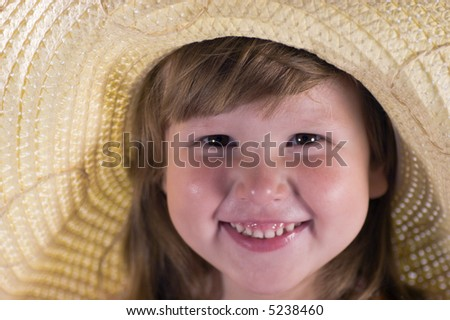 Happy laughing little girl wearing straw hat