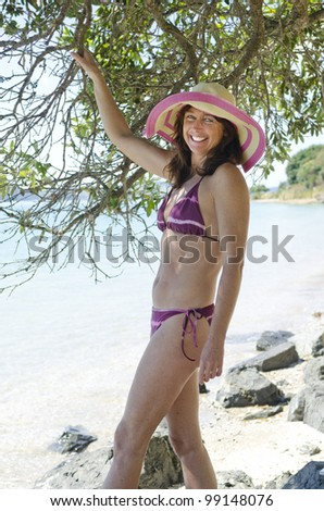 Happy laughing slim woman on beach wearing hat and bikini - stock photo
