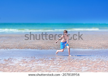 Happy laughing teen age boy running on a beach jumping in sand dunes having fun on a summer vacation on ocean coast enjoying a hot sunny day - stock photo