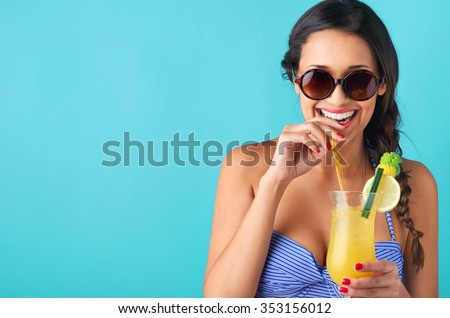Happy laughing woman wearing a bikini drinking a tropical cocktail, isolated on bright blue background