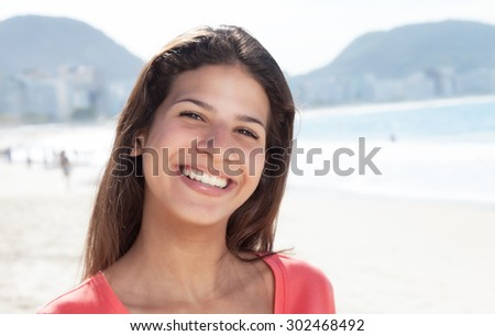Happy laughing woman with dark hair at beach with ocean and blue sky in the background - stock photo