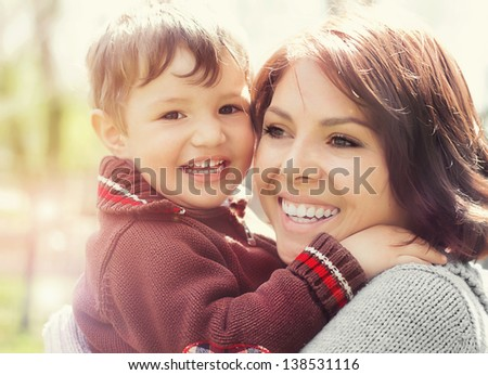 Happy laughing woman with her little son outdoors - stock photo