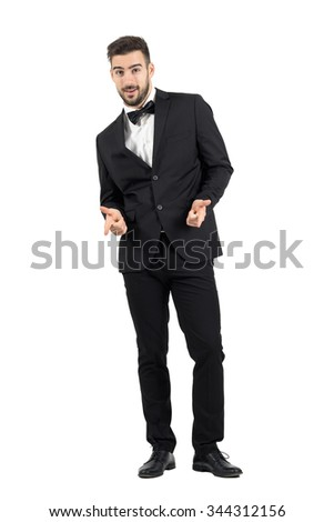 Happy laughing young luxurious man in tuxedo pointing at camera. Full body length portrait isolated over white studio background. - stock photo