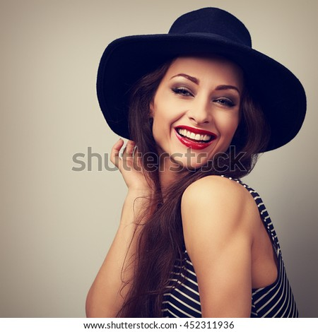 Happy laughing young woman in black hat looking. Vintage bright closeup portrait - stock photo