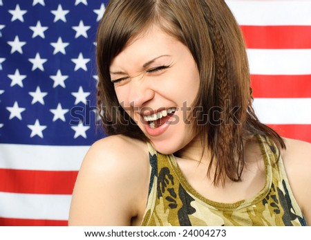 happy laughing young woman standing opposite an American flag - stock photo