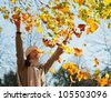 Happy laughing young woman throwing leaves in autumn park - stock photo