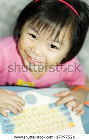 Happy learning. Little asian girl with computer.