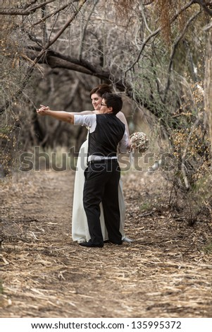 Happy lesbian newlyweds dancing together in forest - stock photo