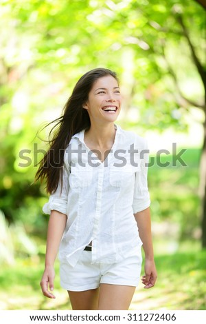 Happy life. Healthy woman walking in spring summer park looking away doing a health walk wearing white cotton or linen casual clothing. Mixed race Asian / Caucasian young female in her 20s. - stock photo