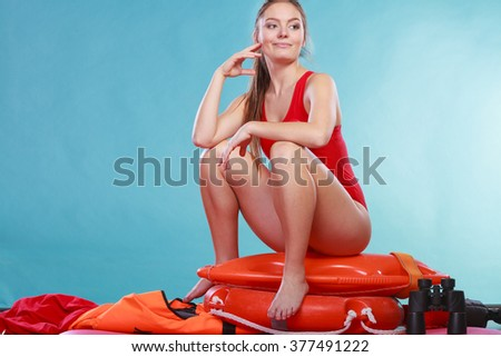Happy lifeguard sitting on rescue tube buoy and ring lifebuoy. Woman girl having fun. Accident prevention and rescue. - stock photo