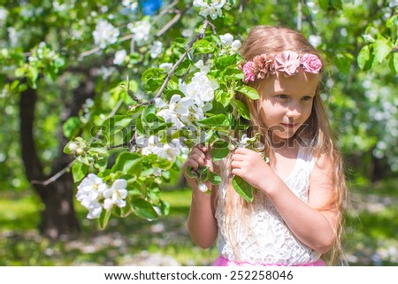 Happy little adorable girl in blossoming apple garden