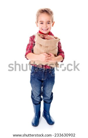 Happy little agriculturist boy holding a sack of red potatoes - stock photo