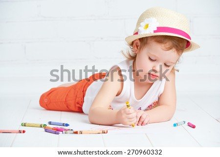 happy little artist  girl in a hat draws pencil lying on the floor - stock photo