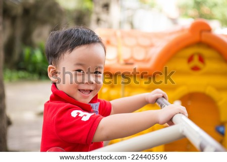 Happy little asian boy, elementary aged child in the garden playground. Summer park. Outdoors. Portrait of a 3-4 years boy playing on soft nature background  - stock photo