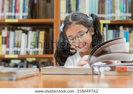 Happy little asian child girl wear eyeglasses reading book school background: Lovely cute young student kid opening flipping book in archive resource collection room: National library lover week