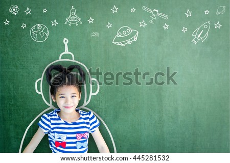 Happy little asian girl kid in astronaut suit doodle chalk board drawing & universe space out of earth planet on school green chalkboard background: World UFO day creative educational conceptual idea