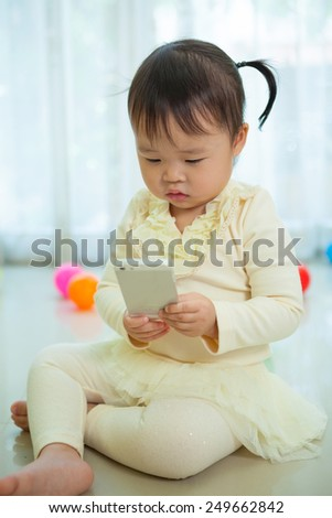 Happy little asian girl using smart phone in the home